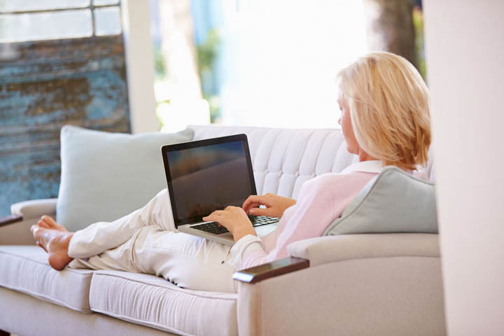 A woman sits on a couch writing on her laptop, looking for dating advice.