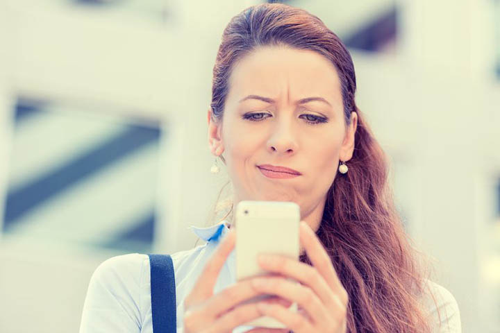 A beautiful woman is confused while reading a text from her boyfriend.