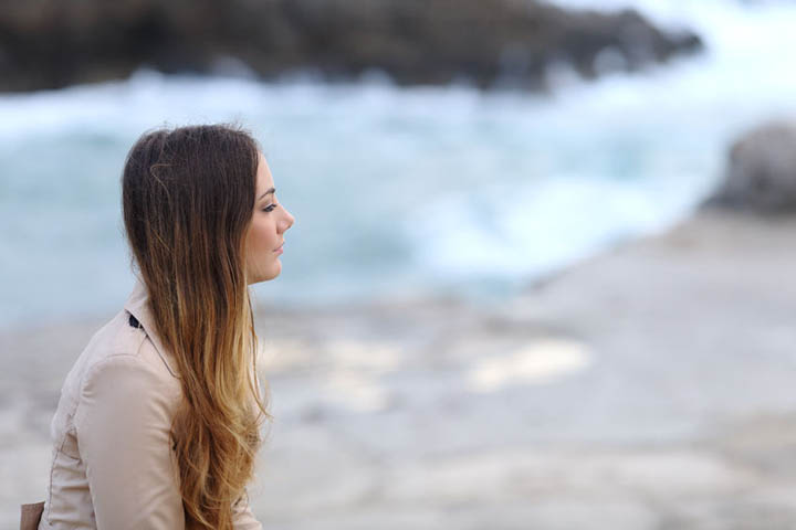 A beautiful woman sits on a beach looking sad because her ex has moved on.