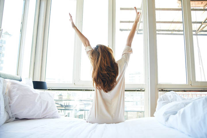 A beautiful woman stretches in the morning thinking about ways to be happy.