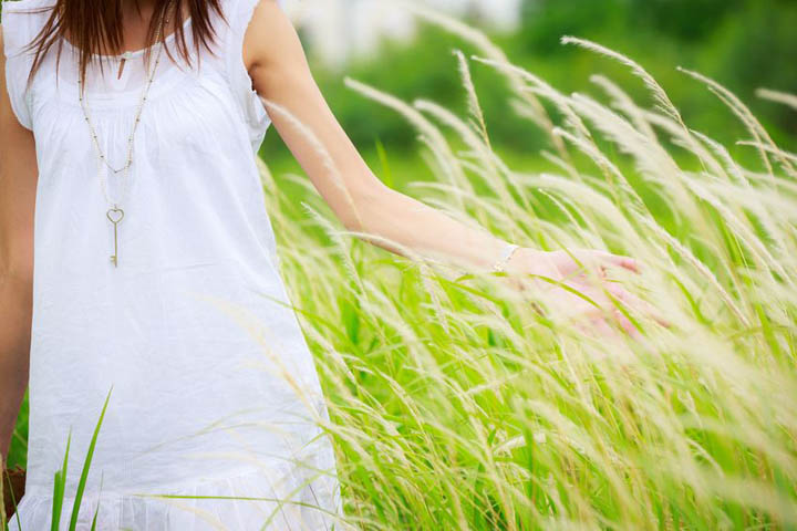 A woman in a white cotton dress is walking through tall grass.