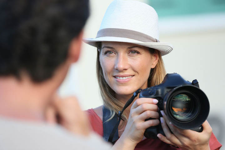 A beautiful woman with camera looking at a man.
