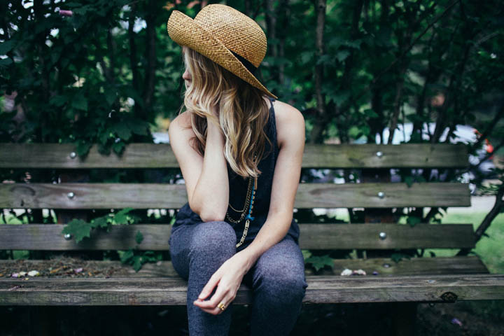 A beautiful woman sits on a bench, looking discouraged, wondering if it will ever work out.