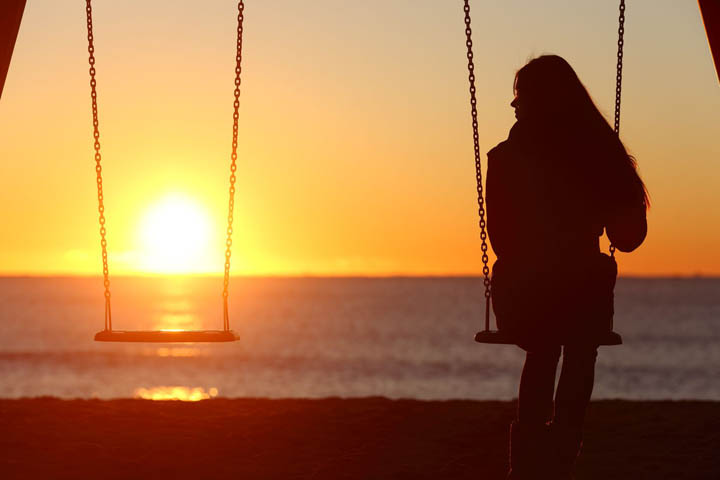 A woman sits alone on a swing looking at the sunset.