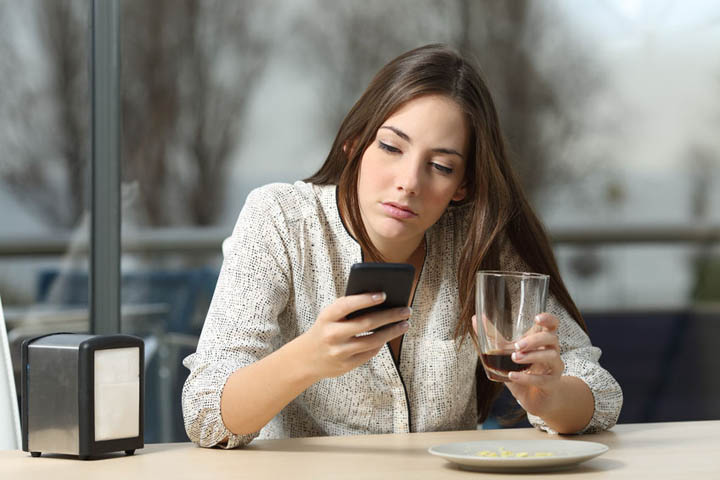 Angry woman stood up on a date in a coffee shop looking at her phone
