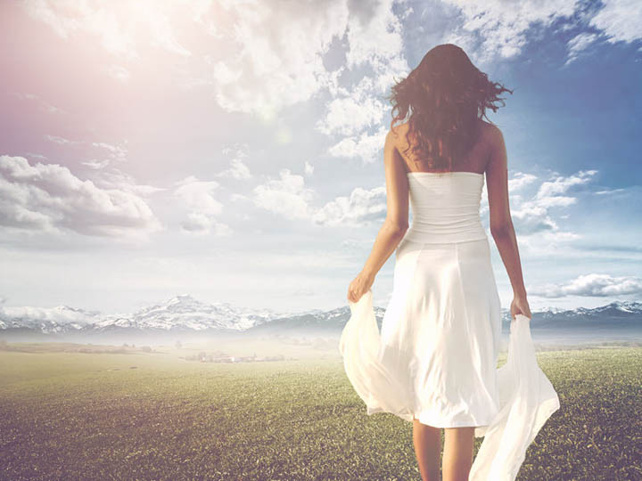 slender long-haired woman wearing white summer dress while walking on a green meadow towards a bright and sunny horizon.