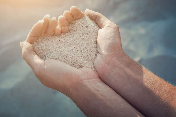 Female hands holding a sand in form of the heart