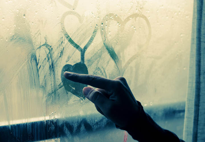 Beautiful 35 year old woman stands in front of the window making hearts on the glass with her finger.