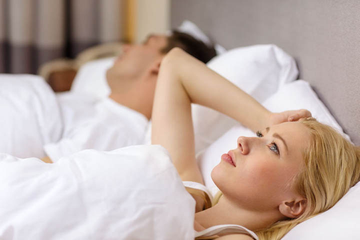 Couple in bed, woman with insomnia, wondering how long to wait for commitment.