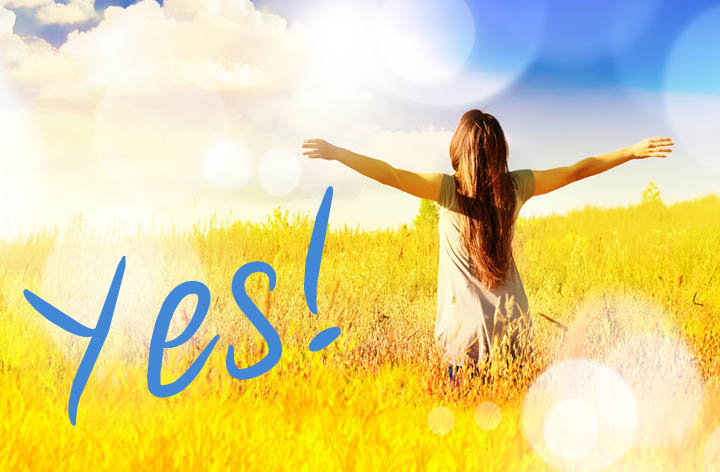 A beautiful woman rising up from the grassy field with her hands in the air proclaiming Yes!