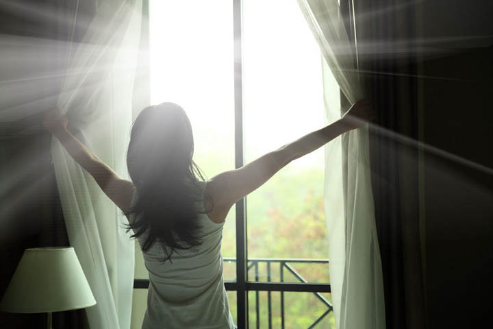 Woman opening curtains in a bedroom letting the light shine on her.