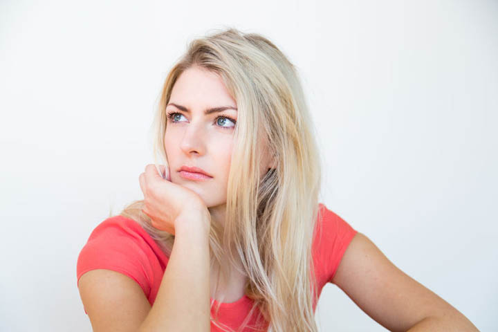 A beautiful woman looks confused and drained with her chin resting on her palm.