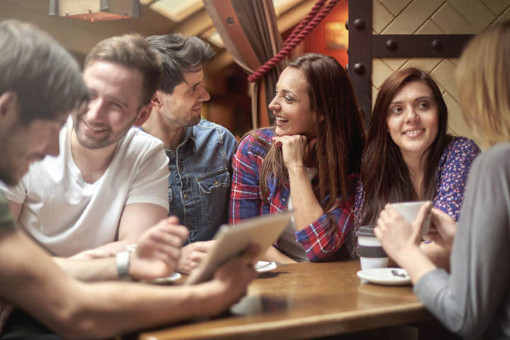 A group of male and female friends are out together socially at a restaurant.
