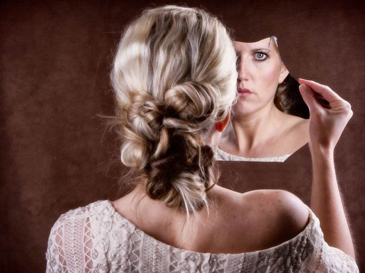Woman looking into a broken mirror representing her low self-esteem.