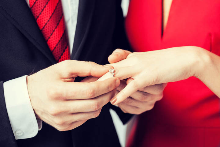 Picture of man putting wedding ring on woman hand signaling engagement.