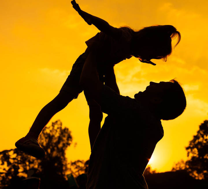 Silhouette of a father and daughter who play outdoors at sunset background.