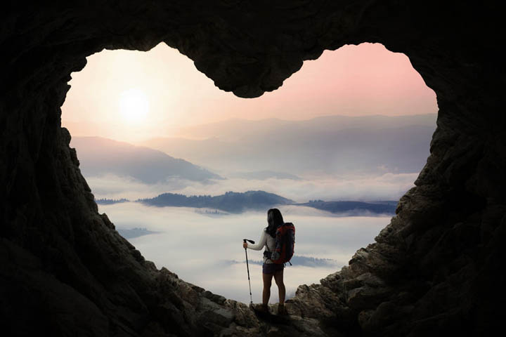 A woman hiking through a heart shaped cave symbolizing going through heartbreak.