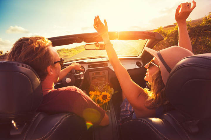 Happy young man and woman driving along country road in convertable at sunset. freedom adevnture roadtrip!