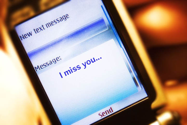 A text message on a mobile phone reads I miss you.