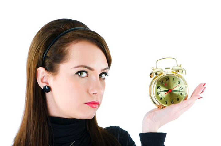 A beautiful woman looking pensive holds a clock wondering if she is wasting her time with her boyfriend.
