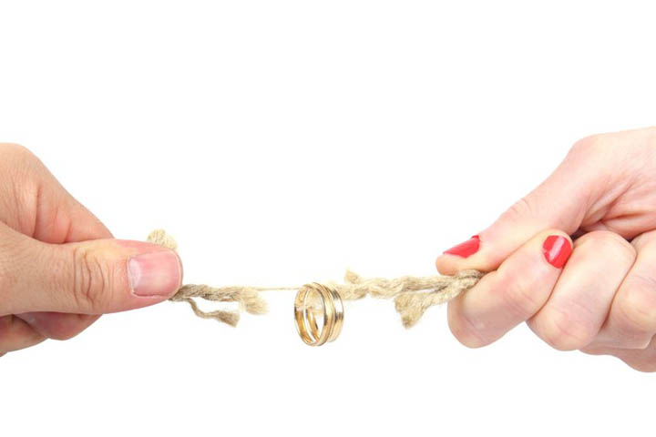 A tug of war between a man and a woman with an engagment ring on a string, signifying non commitment to marriage.