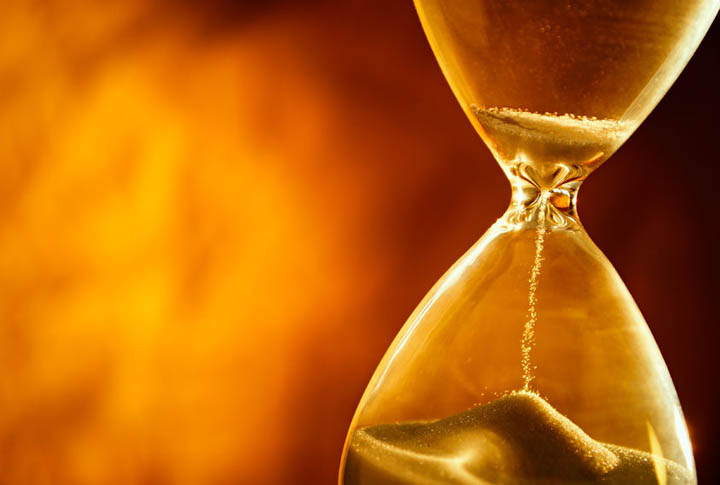 Sand passing through the glass bulbs of an hourglass measuring the passing time representing wasting time in a dead end relationship with a man who won't commit.