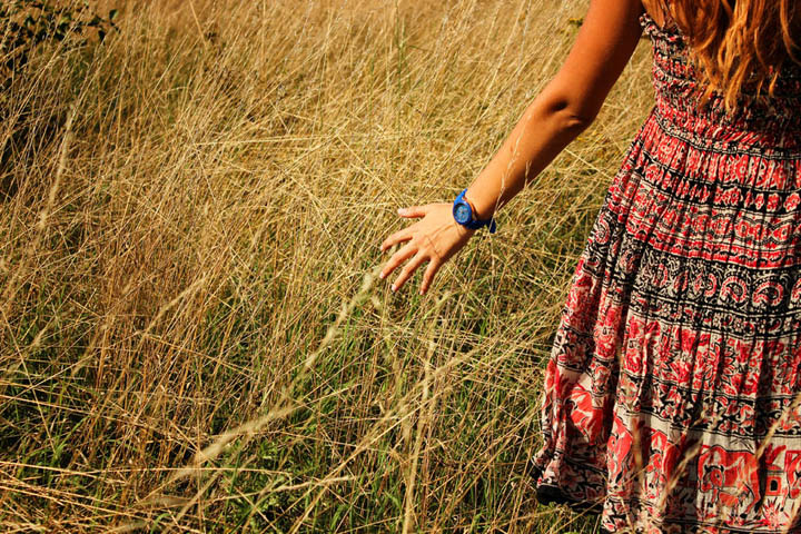 Beautiful woman walking in the field and runs hand through the high dry grass in autumn.