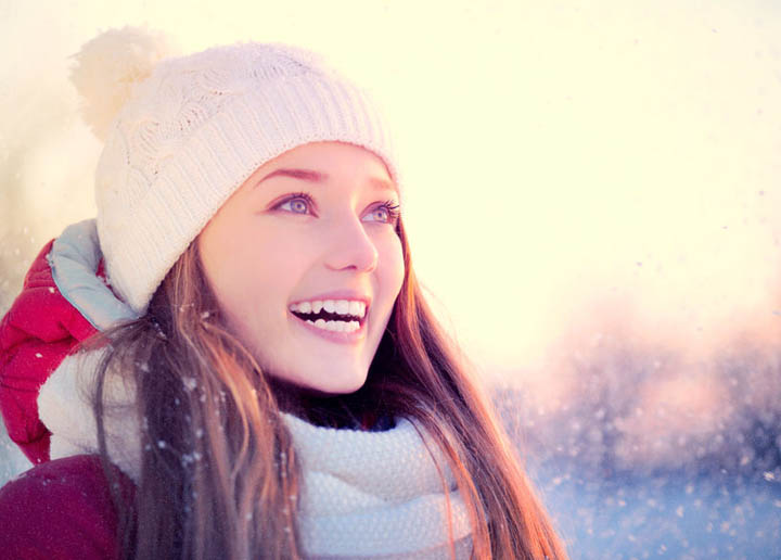 Beautiful woman outdoors in frosty winter park with snowflakes.