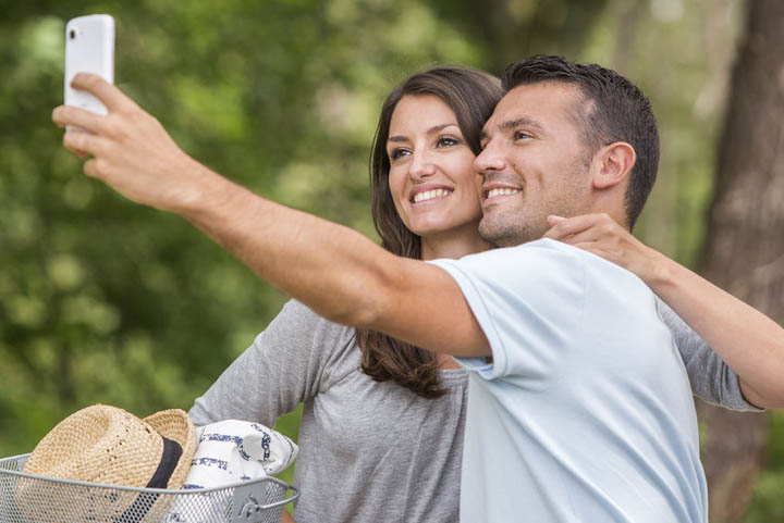 Young couple in love, on bicycles, with man taking a selfie.