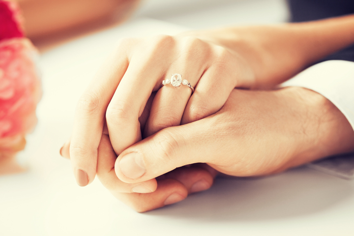 Woman wearing wedding ring holding the hand of her husband celebrating their marriage wedding anniversary