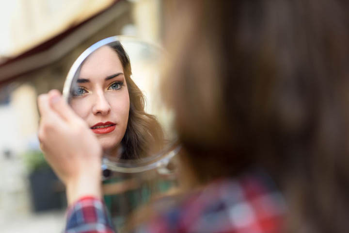 Beautiful woman looking into a mirror.