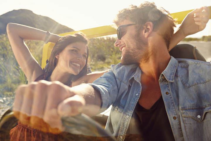 Happy young man and woman in a car enjoying a road trip on a summer day. Couple out on a drive in a open car.