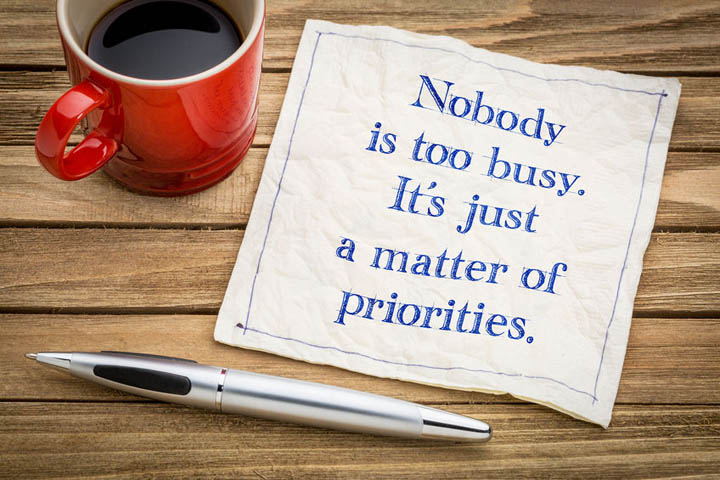 Nobody is too busy, it is a matter of priorities - handwriting on a napkin with a cup of espresso coffee