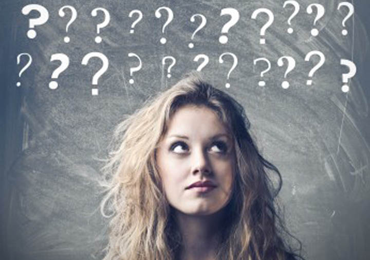 A woman is looking up at question marks above her head.