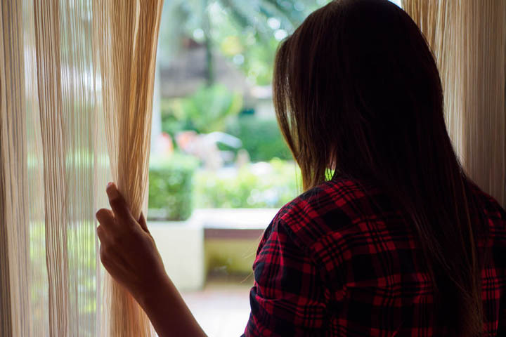 Rear view of a woman holding the curtains open to look out of a large light window at home.