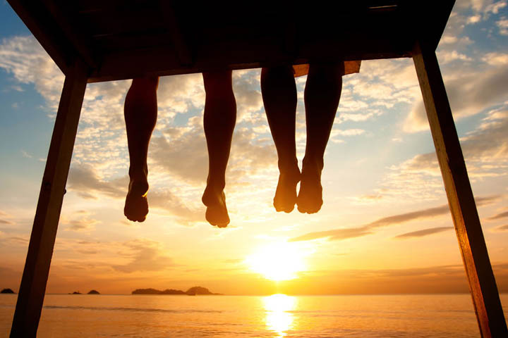 silhouette of feet of couple sitting on the pier at sunset beach, low angle view