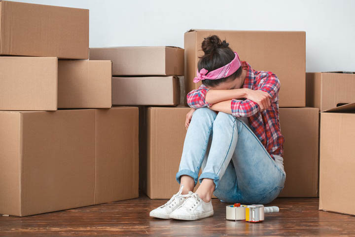 Beautiful woman sitting on floor surrounded by moving boxes face in her hands crying.
