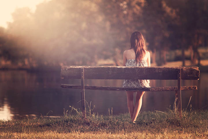 A young girl sits on a bench by a lake, feeling invisible and alone.